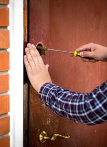 closeup shot of Locksmith Hallandale Beach FL carpenter fixing door lock with screwdriver