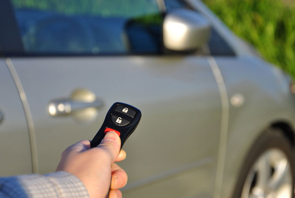 a car and a man holding a car key fixed by a fort lauderdale car locksmith service